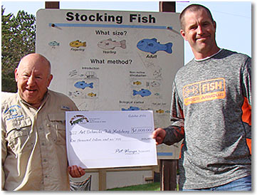 World Musky Hunt President Ron Rickman presents a $1,000 donation for musky rearing to Gary Muench (at right), hatchery supervisor at Art Oehmcke Fish Hatchery.